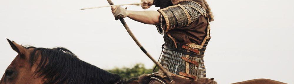Eine Frau mit langen blondn Haar in einer Rüstung auf einem braunen Pferd. Die Frau zielt gerade mit Pfeil und Bogen.