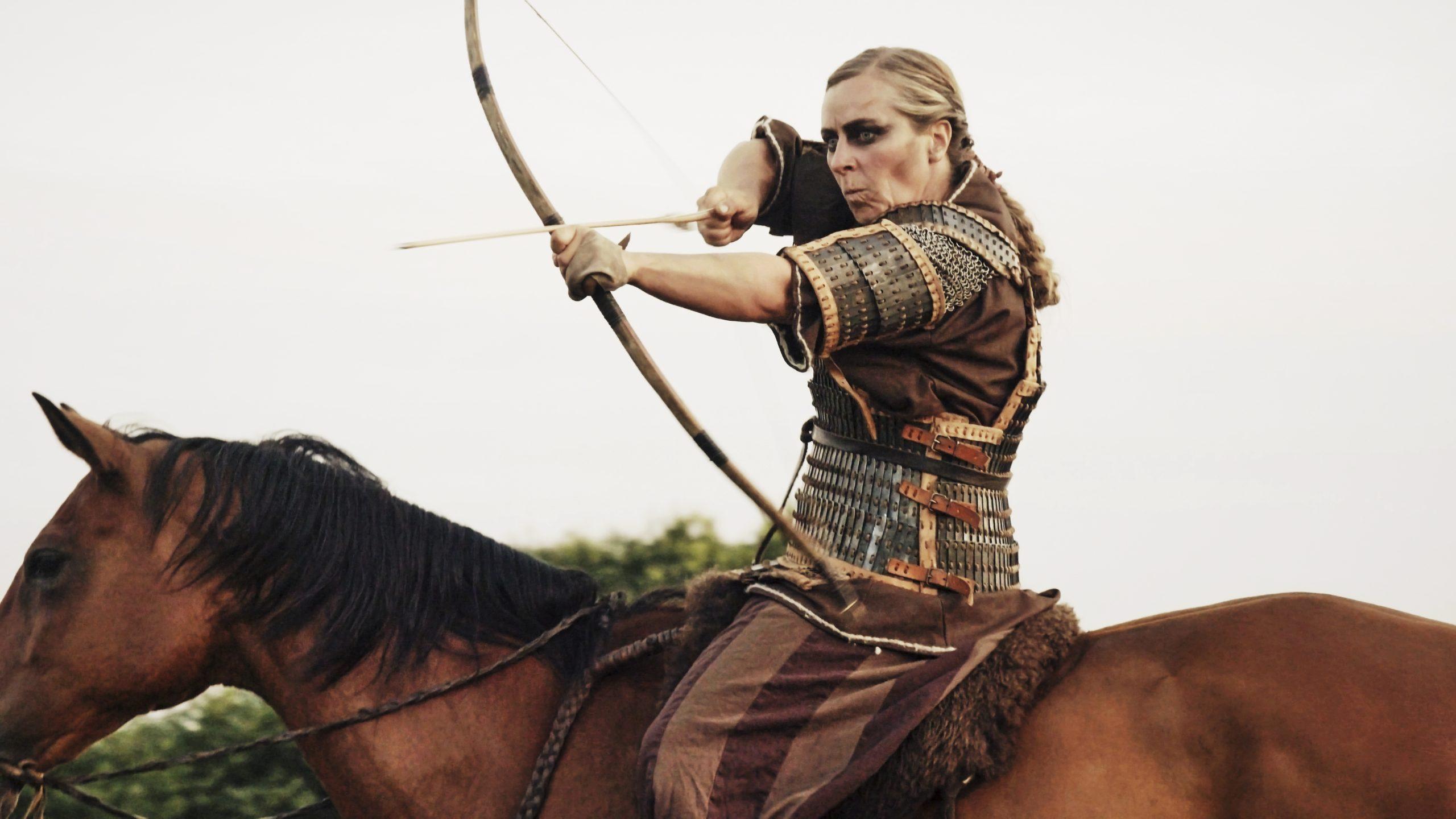Eine Frau mit langen blonden Haar in einer Rüstung auf einem braunen Pferd. Die Frau zielt gerade mit Pfeil und Bogen.