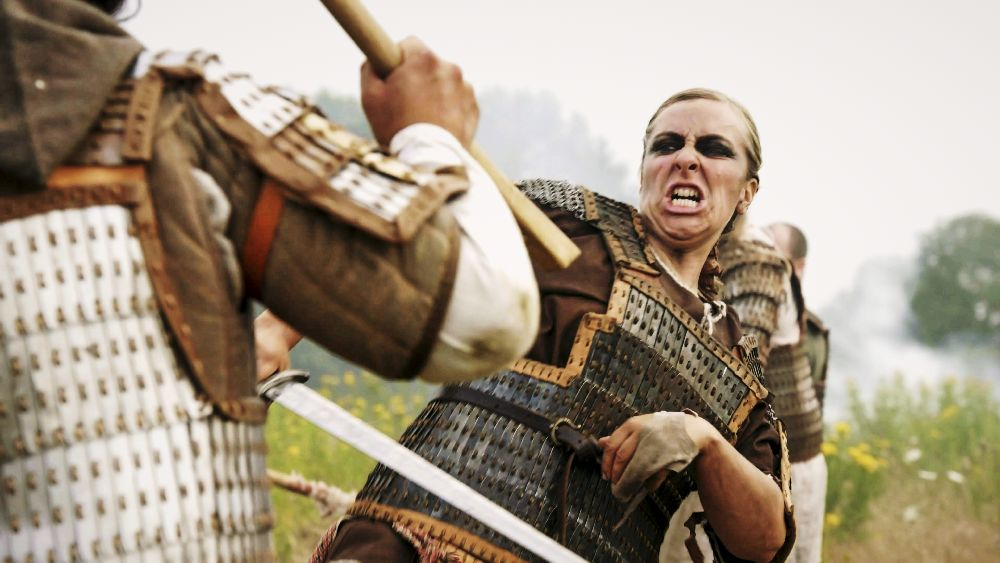 Eine Wikingerkriegerin im Kampf. Die blonde Frau ist ein einen Schwartkampf verwickelt.