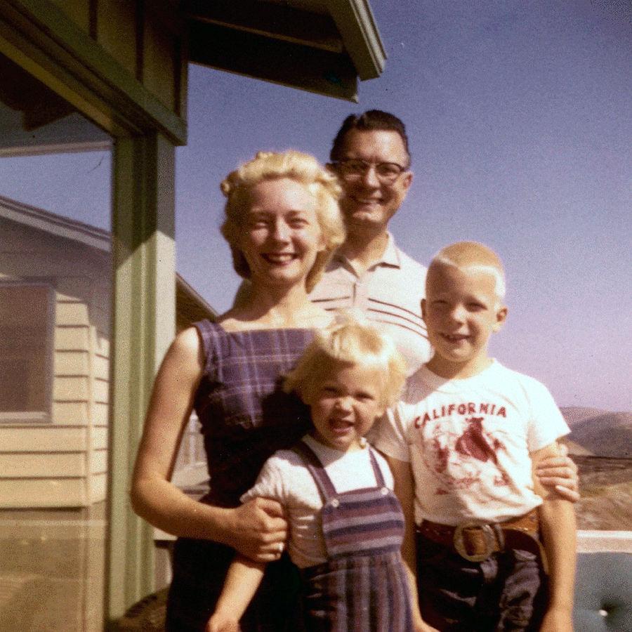Eine klassische weiße Familie aus den 50ger Jahren. Vater Mutter und zwei Kinder. Sie sind Blond und weis. Die Männr Tragn Hosen, di Frau und das Mädchen tragen Kleider.