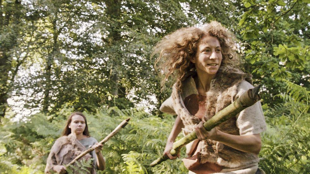 Eine Jägerin in einem Wald. Sie ist mit Fell gekleidet, und Rennt mit einem Speer durch die Grüne Natur dierekt an der Kameraposition vorbei. Im Hintergund ist ine weitere Jägerin zu sehen.