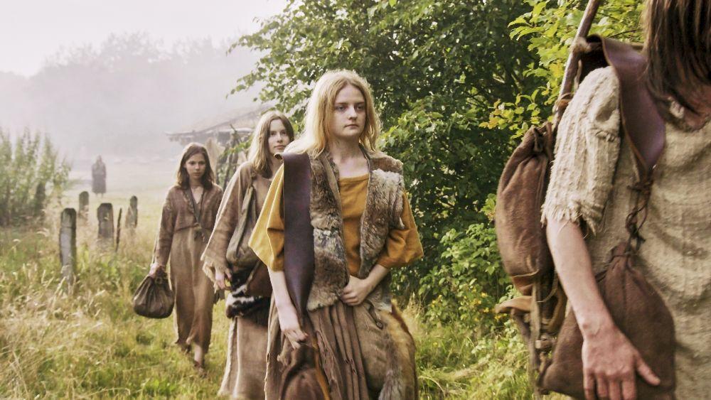 Eine Gruppe Frauen läuft im Gänsemarsch durch die Natur. Sie tragen Kleidung aus einfachn Stoffen und Fell.