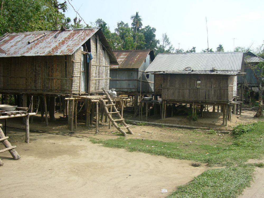 Drei aus Holz und Blech gebaute Pfahlbauten, die auf dem Land stehen.