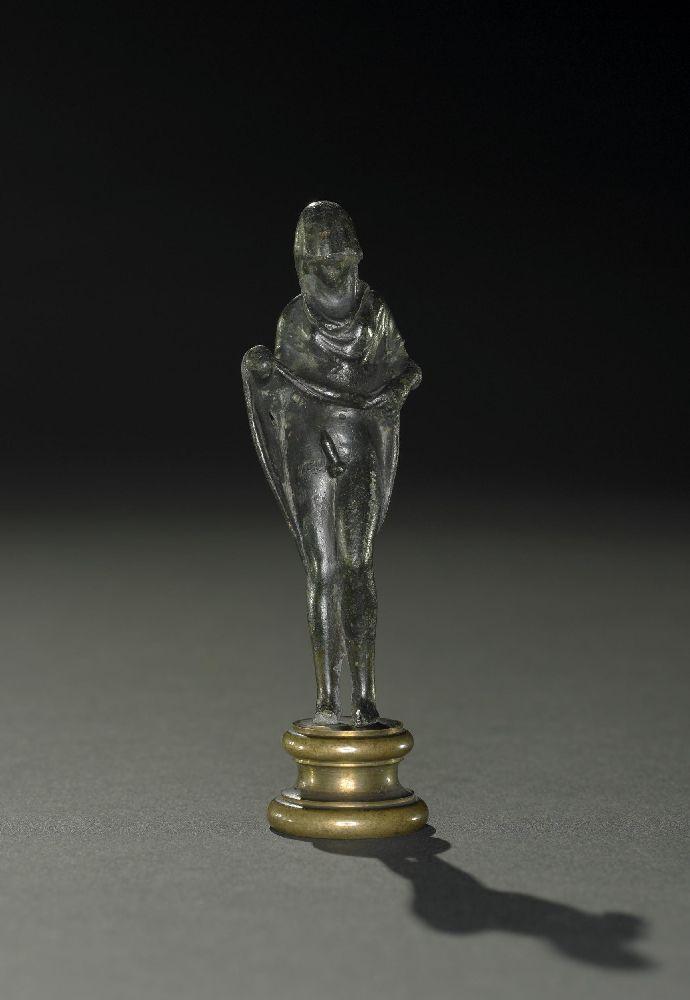 Eine kleine Bronzfigur auf inm vrgoldten Sockl. Zu shen ist in wohlig gbaute Frau, mit inm vrmummten gsicht. Si hält ihren Rock hoch, wodurch in ein rrigierter Penis sichtbar wird.