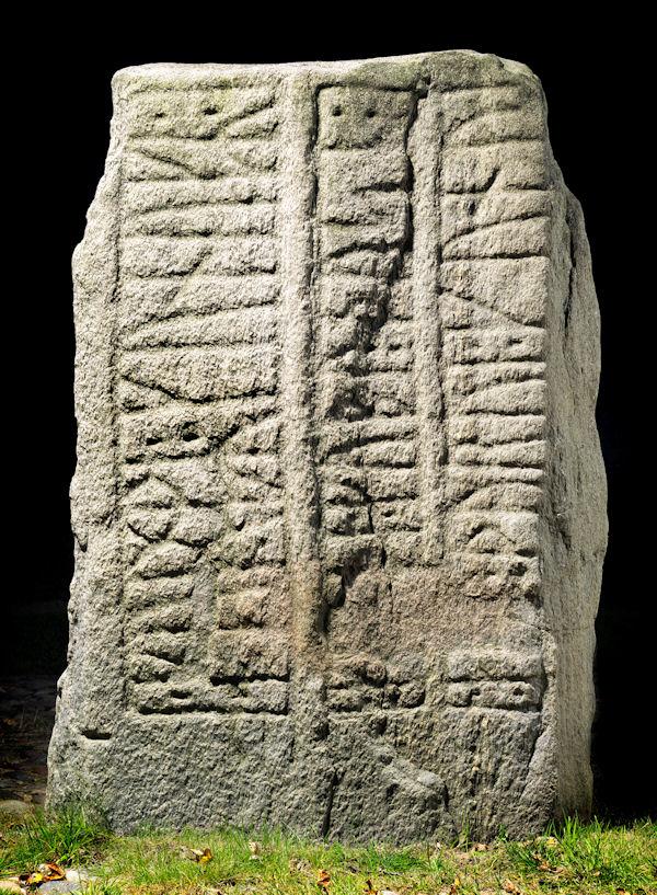 Der kleine Runenstein von Jelling mit Fokus auf die Runeninschrift.