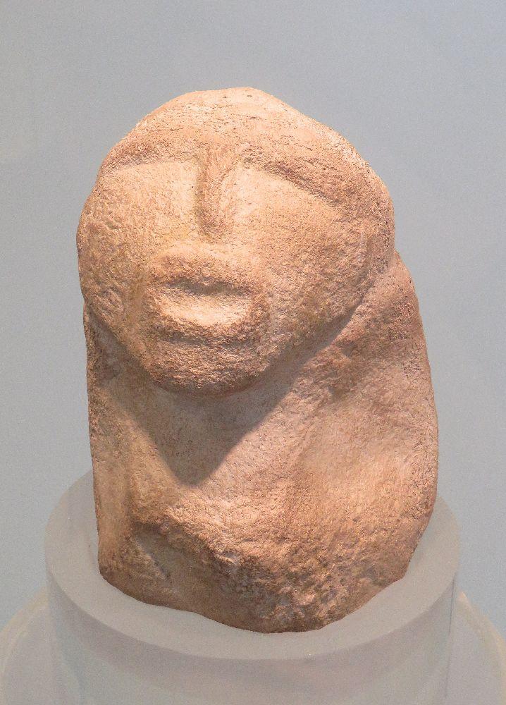 Eine Figur aus Lepenski Vir. Sie hat einen Kopf mit inem hrausgarbiteten gsicht, der auf inem Körpr sitzt, dr nur auf inm Klumpen besteht.