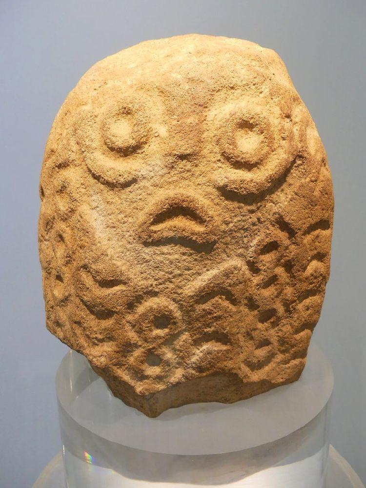 Ein Figur aus Lepnski Vir. Si hat viele Ornamente und in der mitte ein Gesicht. Die Augen sind kreisrund, und der Mund ist Schlauchartig und mis gelaunt nach unten gebogen.