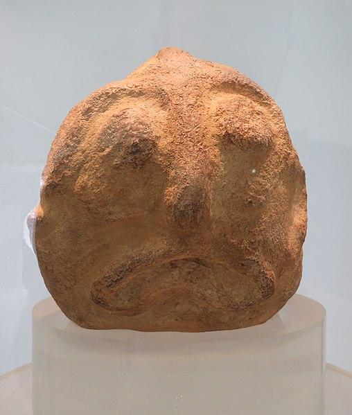 Ein Terrakottafarbnr Stein. Er ist Rund, und zwi Kuglrunde Augen, eine Nase und einem Schlauchartiger nach unten gebogener Fischmund sind in den Stein graviert.