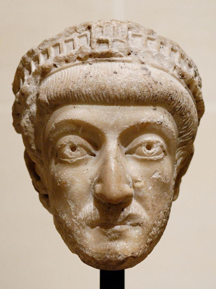 Ein Kopf von Theodosius II. Es handelt sich um den Teil einer Marmorskulptur. Die Augen sind gebohrt, Die Nase ist groß und ein Bisschen hakig. Das Haar wird mit einer Art Diadem gerafft.