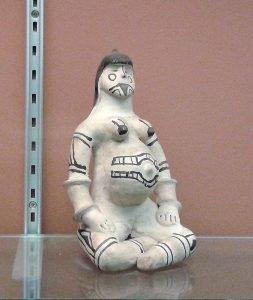 Eine Keramikpuppe einer schwangeren Frau. Es ist eine Litjoko der Karaja. Die Frau iat ganz in Weiß dargestellt und mit schwarzen strichn bemalt.
