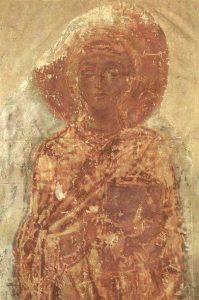 Darstellung der Heiligen Thekla. Ein Relief das rot bemalt ist. Eine Frau mit einem Heiligenschein.