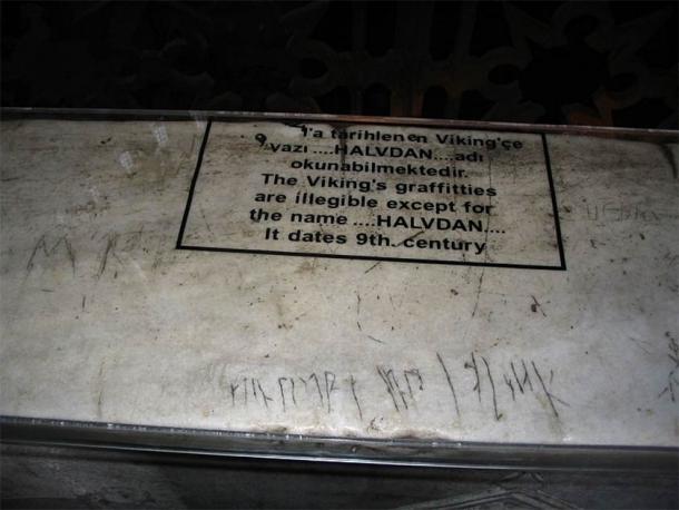 Ein Ausschnitt ins Marmorgländers. In das Material reingeritzt steht ein Satz. Darüber ist in schild mit einer übrstzen Erklärung.