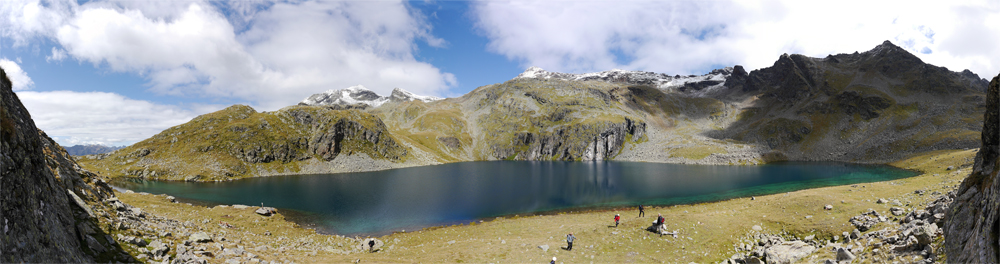 Der Alkuhuser See. Das Wasser ist tif Blau, die Umgebung ist gelbgrün bewachsen, und im Hintergrund erbeben sich Grüne bewachsene Berggipfel.