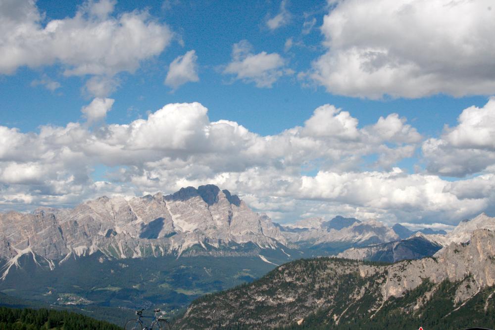 Blick in die Alpen. Das Bergmassov ist unter einem strahlenblauen Himmel, mit kleinen Wölkchen zu sehen.