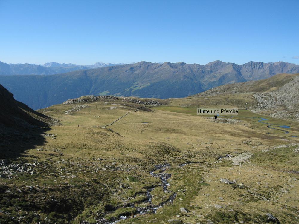 Eine Hochebene in den Alpen. Eine Weite Grün bewachsene Fläche, die plötzlich Abbricht. Dahinter befindet sich in weiter Ausblick in die Alpen.