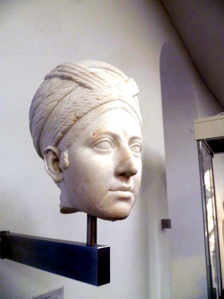 Der am Hals abgebrochene Kopf der Marmorskulptur einer Frau. Die Frau hat ein ovales Gesicht, eine Gerade Nase und mandelförmige Augen. Die Frau trägt einen geflochtenen Turban.