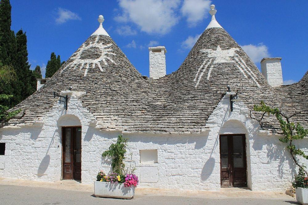 Zwei in Reihe gebaut Trullihäuser. Sie haben weiß gekalkt Wände und weiß gemalte Sybole auf dem Dach.