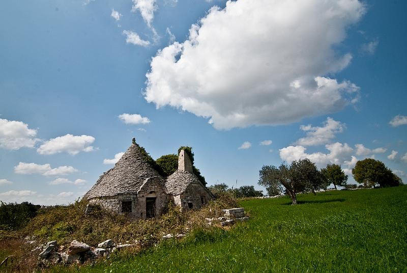 Ein Bauernhof mit drei Spitzen Dächern auf einer grünen Wiese.