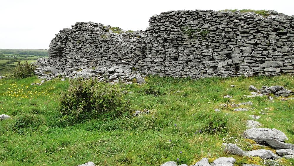 Die innere Kalksteinmauer der Burganlage. Sie ist bis zu 4 Meter hoch. und erhabt sich im Rechten Winkel von der grünen Wiese.