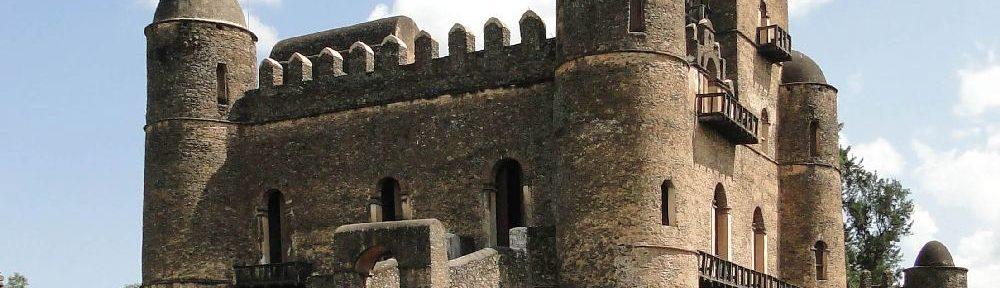 Ein Palast aus Grau-gelb-Rötlichen Sandstein. Es ahandelt sich um inen zweigeschossiegnbau mit Türmen an den Ecken, die auf das flache Dach Aufgsetzt sind. Di Türme habn Kuppeln und sind rund. Ein Bergfried dr viereckieg ist zieht sich in die Höhe. Er hat die dr rst des Gebäudes Burgzinnn mit einem halbrunden Aufsatz.