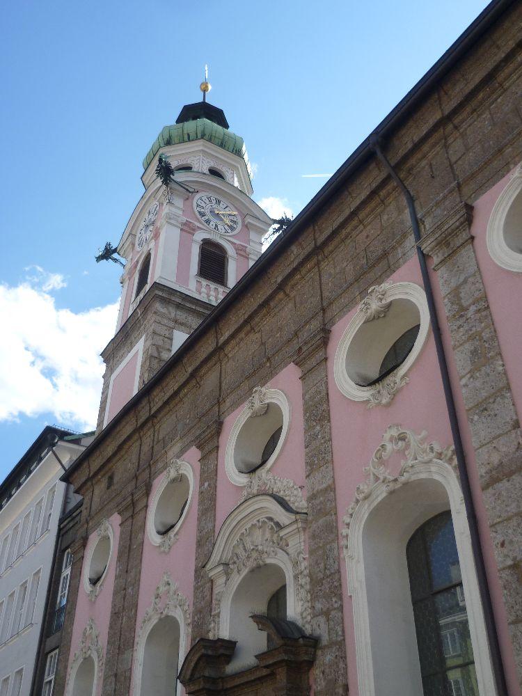 Die Spitalskriche von Innsbruck aus extremer Froschperspektive. Die Kirche ist Rosa gestrichen. Eine Reihe runder Fenster ist zu sehen. Und ein Turm mit einem grünen Zwiebeldach aus Kupfer.