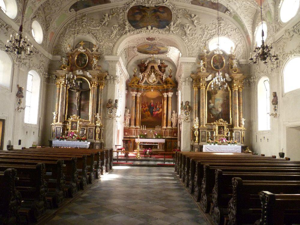 Der Innenraum dr Innsbrucker Spitalskirche. Ein Gang in der Mitte, links und rechts gesäumt von Holzbänken führt zu dem Chor. Dieser Ist mit Stuck und drei Barockaltären ausgestattet.