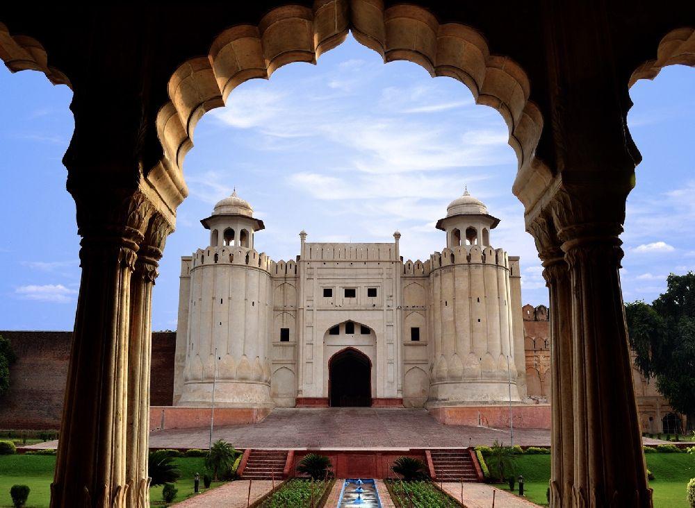 Ein Tor das mehrere Stockwerk Hoch ist aus Weißem Marmor, an einer Festungsmauer aus rotem Sandstein, Das Tor hat zwei Runde Türme, und einen geschwungenen Torbogen.