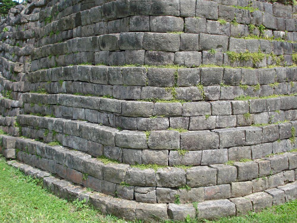 Ein Stufig aufeinander errichtets Mauerwerk. J zwei schichtn fein behauener grauer stein liegn dabi exakt aufeinander, darüber ist die Wand je nach innen versetzt. Die Bauweise wirkt filigran.