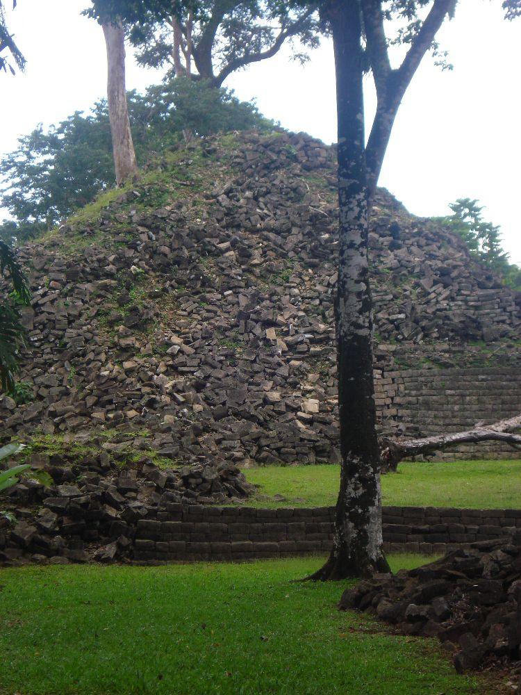 Der Rest einer Pyramiede aus grauen Stein. Die Pyramiede ist zur hälfte vollständig in sich zusammen gefallen. Überall liegen Steine Hrum, sie Kullrn von dem Bau herunter.
