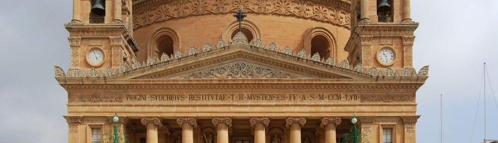 Die Kuppelkirche Von Mosta. Ein Bau der vo Vorne den Parthenon nacharmt. Über ihm türmt sich ine Große Kuppel auf. Das Gebäude bestht aus Orange-gelben Sandstein