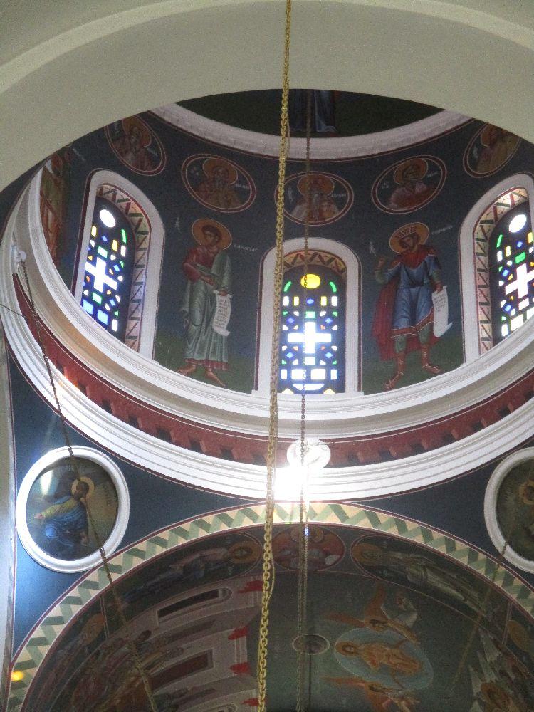 Malerei in der Kuppel von Megali Panagia. Die Kuppel ist blau bemalt. Vor diesm Hintrgund sind einig Darstellungn Von Heilign zu erkennen, die zwischen bunten Fesntern mit Kreutzintarsie dargestellt sind.