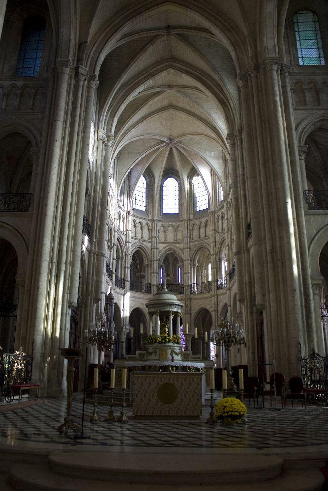 Der Chor der Kathdrale von Noyon von innen gesehen. Licht scheint durch Fenster hinin, dennoch wirkt s ein bisschen Düster.