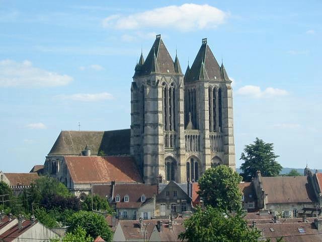 Die Kathedrale von Noyon thront über dr Stadt. Deutlich sind zwi Hohe viereckiege Kierchtürm mit einem Zpitzn Schindeldach zu rkennen. Auch das Dach der Kirche Selbst erhebt sich über die Stadt. Die Kirche berragt den Ort Noyon um mehrere Stockwerke.