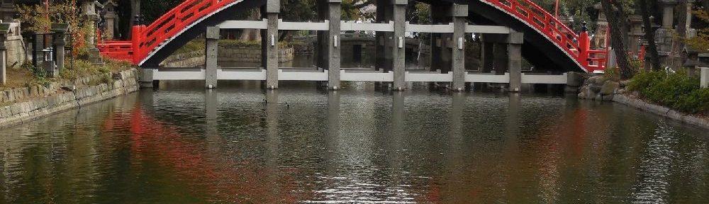 Eine Regenbogenförmige Brück über einn Fluss. Die Brück ist sehr rundlich und hat ein Zinoberrotes Geländer.