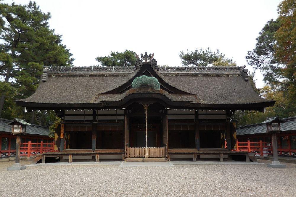 Ein aus Holz Gbautes Schreingbäude mit einm Strohdach. Der Eingang besteht aus einem Quer gelegten Giebel, mit einm Geschwungenen Dach. Dem Schrein ist eine Art Veranda Vorgelagert.