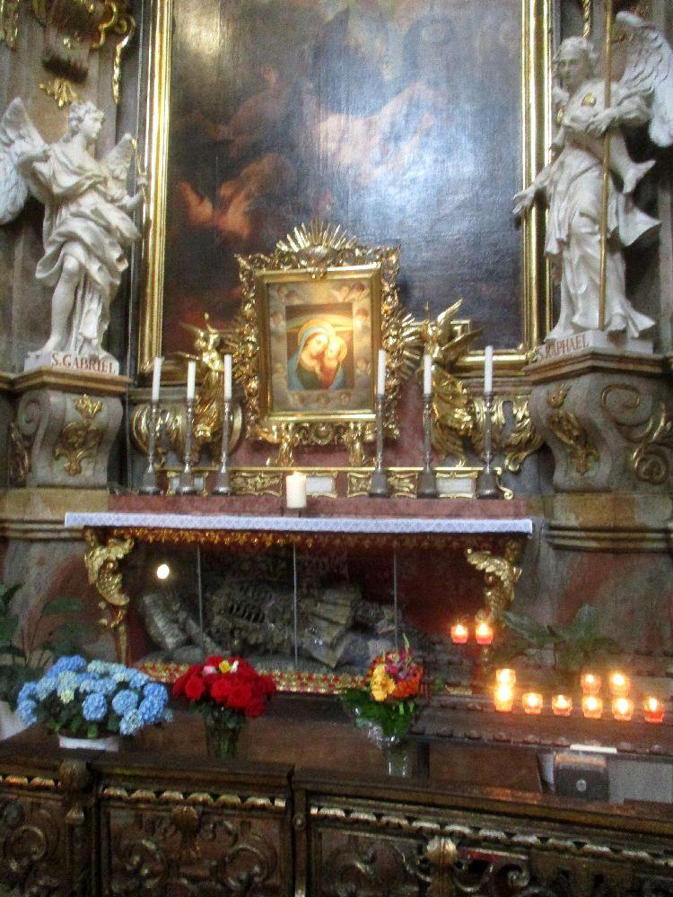 Der Reliquinschrein mit dem Heilign Benediktus in der St. Peterkirche. Der Leichnahm befindet sich in einem gläsernden sarkophag. Über ihm Ist ine Darstllung der Maria mit kind, in Form von der Ratgeberin. Dahinter befindet sich ein Großes nur halbforografiertes Gemälde, das einen Erzengl Zeigt, der andere niederringt. Links und Recht der Gesammtszenerie befinden sich zwei weitere Marmorfiguren, si verkörpern zwei weitere Erzengel