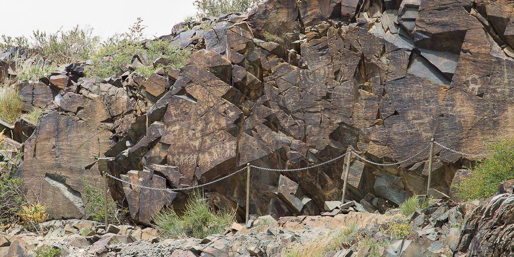Zersprengt Felsen mit Ritzungen aus Tamgaly. Die Bilder zigem Zwei Groß Sonnenmenschen un dadruntr klin tanzende strichmännchen.