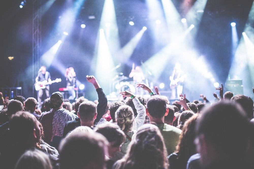 Ein Menschenmnge von hinten gesehen, viel Leute Tanzen. Sie werden mit blauen und weißen Scheinwerfern angestrahlt, Im Hintrgrund ist eine Bühne zu sehen, die Musiker werden von den Scheinwerfern überstrahlt.
