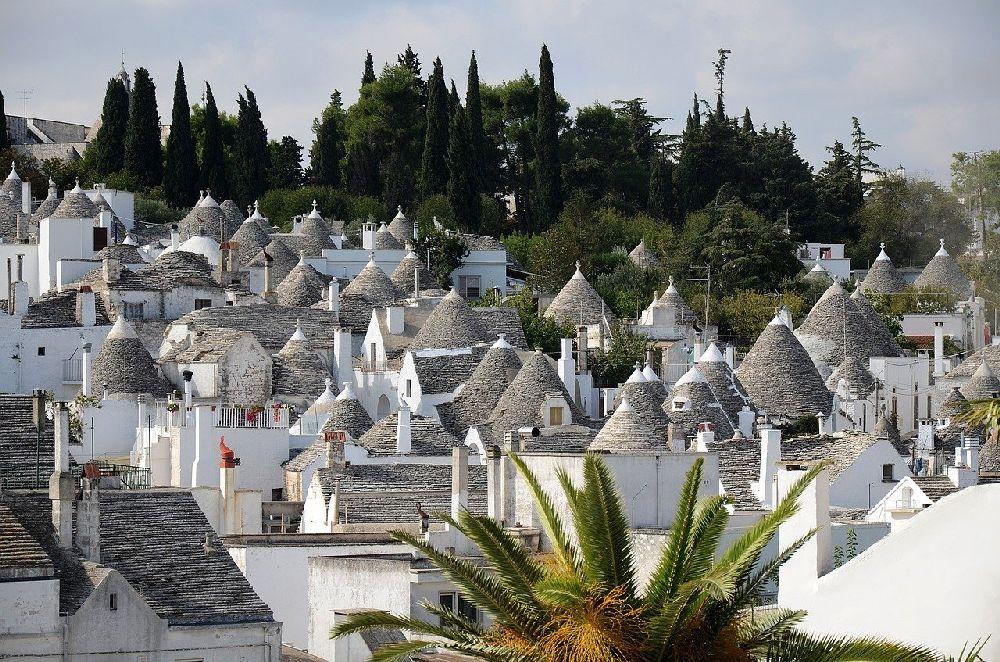 Ein Dorf, dass sich an einen Hang kuschelt. Das Dorf besteht aus Trullihäusern. Es sieht aus als würden alle Häuser Zipfelmützen tragen.