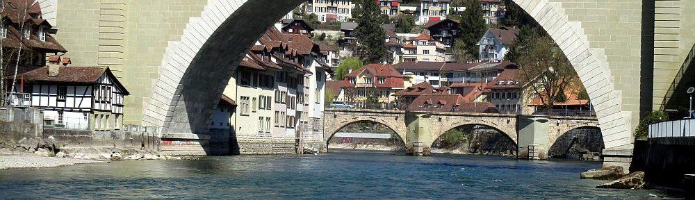 Eine Brücke mit inm riesiegen Bogen führt übr den Blauen Fluss Aare. In Endfernung dahintr ist eine weitere Brücke aus mehrren Bögen zu sehen.