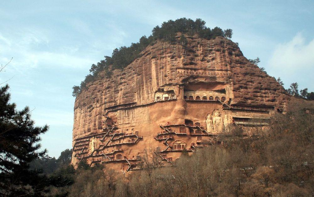 Der Berg Maijishan in China. Ein Roter Sadsteinberg auf dessen Oberkannte Bäume Wachsen. Der Berg Schiebt sich wie ein Finger aus der Erde nach oben. A der Wad sind Zahlreiche Treppen und Balkone errichtet auch Reliefs sind zu sehen