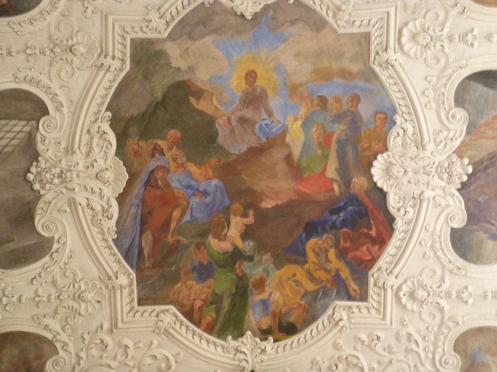 Ein Deckenfresko gerahm von aufwendigem Stuck. Das Fresko zeigt ein Szenerie mit viln Figuren, die zu einem Jesus hinauf Sehnen. Dieser ist mit einem sonnenartig scheindnen Heiligenschein ausgestattet.