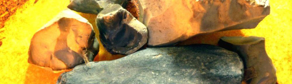 Ein Haufn Steine Liegt auf einer Weltkarte. Es handelt sich um Verschiedee Flintsteine. Sie sind Weiß, Dunkelblau, Braun und Grau.