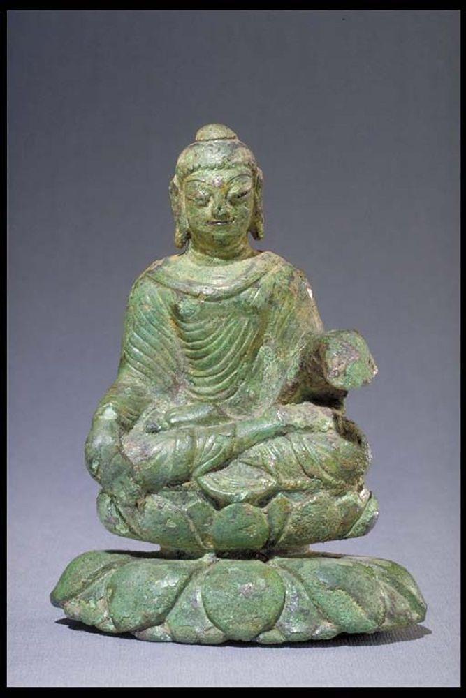 Eine Buddhastatue aus Grünem Jadegestein. Der Buddha sitzt im Lotossitz. Die Linke hand ligt auf sinem Knie, die rechte ist erhoben aber abgebrochen.