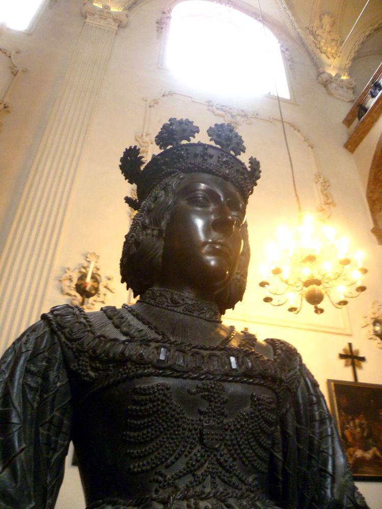 Eine schwarz-Braune Bronzeskulptur. Ein Frau mit einer Königskrone in einem aufwändigen Gewand.