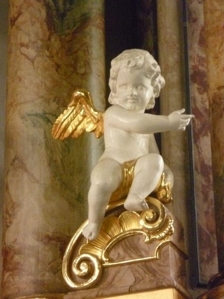 Ein Engel sitzt auf einem kleinen Vorsprung. Eine Kleine Marmorfigur die ein kleinkind zeigt mit goldenen Flügeln.