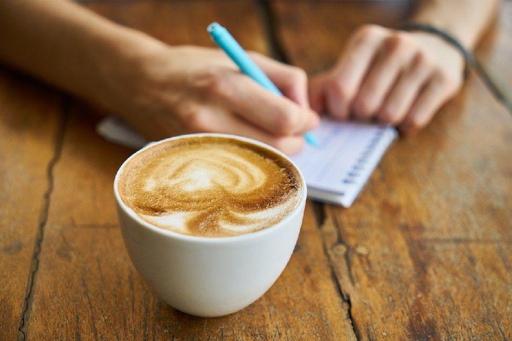 Ein gefüllte Kafftass auf inem Tisch. Dahinter sind zwei Hände die etwas auf einem Schreibblock Notieren