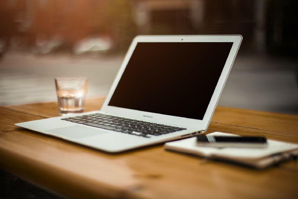 Ein aufgeklappter Laptop, dr Ausgeschaltt auf einem Tisch liegt.