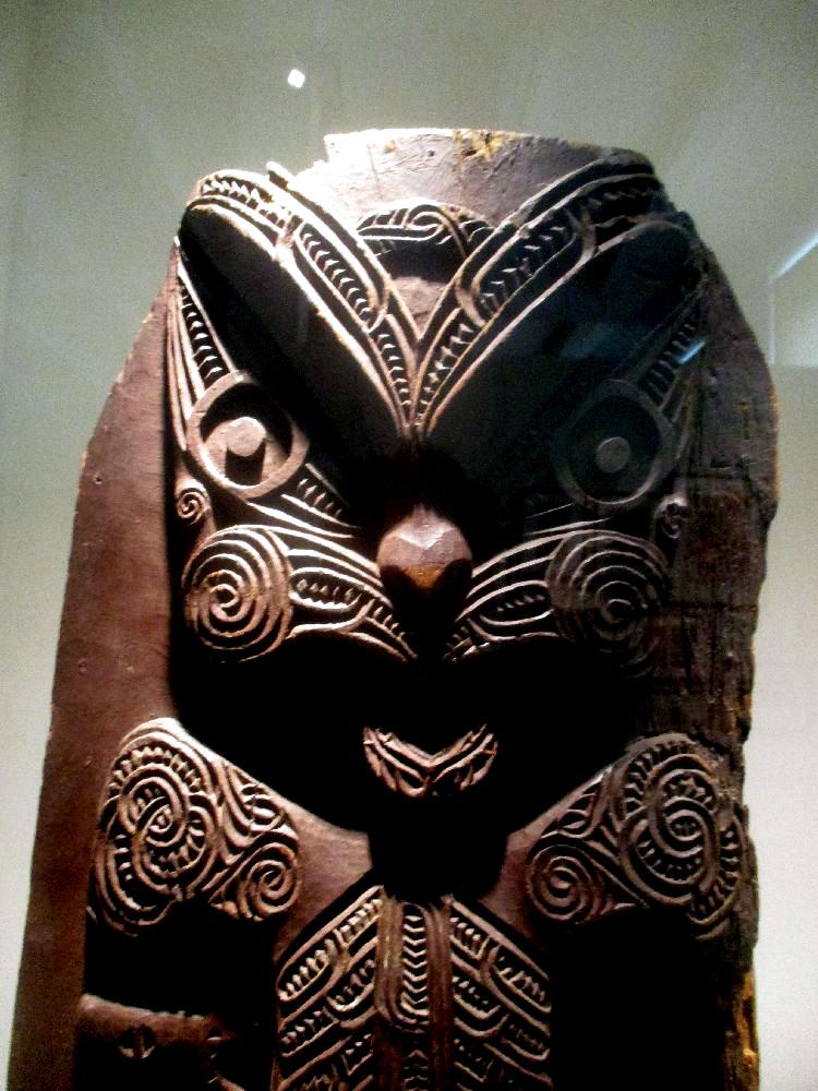 Ein Poupou mit einem Katzenähnlichen Gesicht. Es besteht aus Dunklem Holz