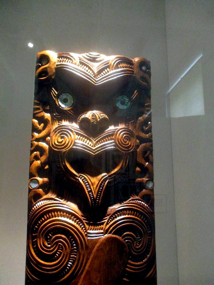 Ein Poupou aus gelblichen Holz. in Art Bär, der die Zung raus streckt